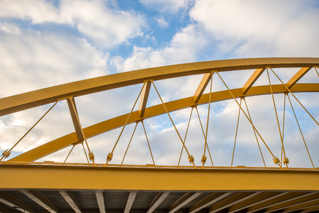 Yellow bridge showing beams and cables against a blue sky Standard-Bild