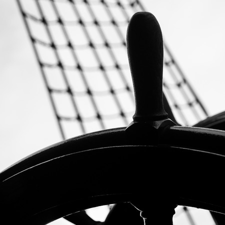 rope ladder: Steering wheel of a ship with rope ladder in the background Stock Photo