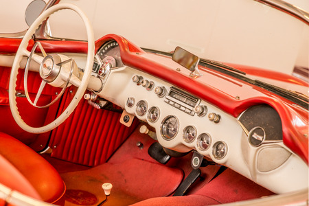 steering wheel and dash board of a red classic American car