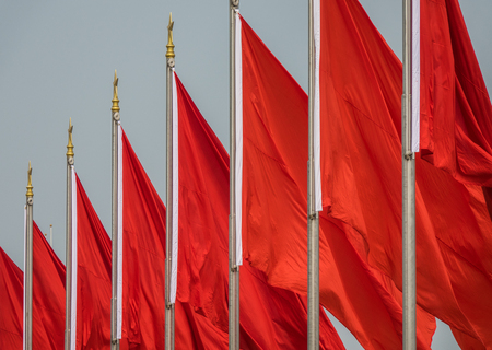 Red flags on poles waving in the wind