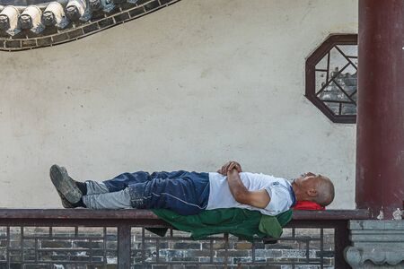 JOHANNESBURG  SOUTH AFRICA-AUGUST 11 2019: A black man worker is resting on a bench. He is sleeping and lying on his work coat. It is quit common in Asia to have a nap during lunch break. Clearly he  에디토리얼