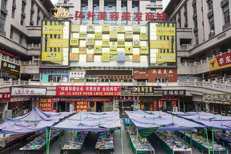 BEIJING / CHINA-JULY 21 2017: Covered book market in the center of the city. The surrounding shops compete with each other with screaming billboards and neon lights. Because there are sails stretched over the stalls, the market can also continue when it r 報道画像