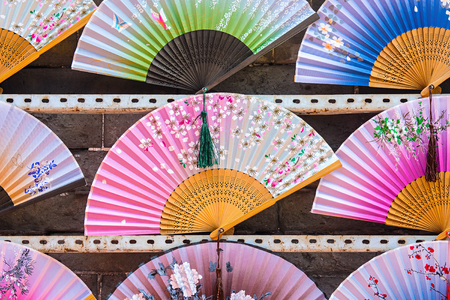 Different colors of hand fans are displayed for sale. People usually use them in warm and tropical areas to give themselves a sense of coolness 写真素材