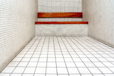 The very sober interior of a prison cell: tiled walls and a wooden bench. The prisoners stay here for a short time only