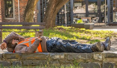 JOHANNESBURG  SOUTH AFRICA-AUGUST 11 2019: A black man worker is resting on a low brick wall. He has put his arm over his head, making it seem like he is sleeping. He is wearing a reflective jacket a