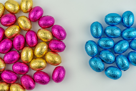 Group of chocolate easter eggs in blue, yellow and pink paper. They are isolated on a white background