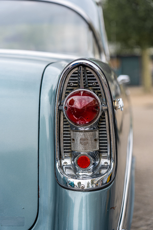 close up of a taillight of a tough yellow american car from the fifties. These cars are characterized by the many chrome and large chassis. Low angle
