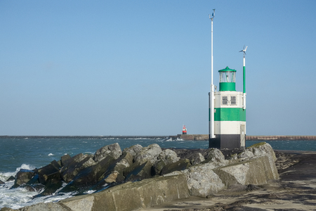 Red and green light house at the shore of IJmuiden in the Netherlands. The lighthouses are intended as a beacon for shipping, but can also be seen in a conceptual sense as a metaphor for leadership and leader Standard-Bild - 125472719