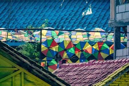 brightly colored facades and roofs of houses in a neighborhood of Malang, Indonesia. This neighborhood attracts the attention of many tourists Standard-Bild - 130817754