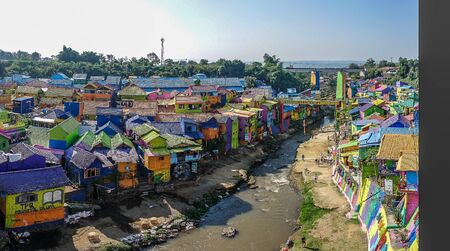 brightly colored facades and roofs of houses in a neighborhood of Malang, Indonesia. This neighborhood attracts the attention of many tourists Standard-Bild - 130817755