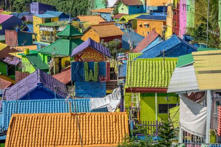 brightly colored facades and roofs of houses in a neighborhood of Malang, Indonesia. This neighborhood attracts the attention of many tourists
