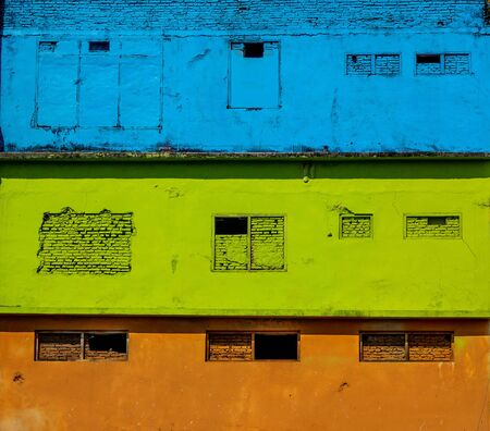 brightly colored facades and roofs of houses in a neighborhood of Malang, Indonesia. This neighborhood attracts the attention of many tourists Standard-Bild - 130817758