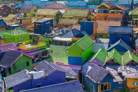 brightly colored facades and roofs of houses in a neighborhood of Malang, Indonesia. This neighborhood attracts the attention of many tourists Standard-Bild - 130817785