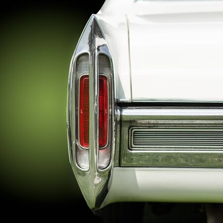 Close up view of a tail light of an American car. The light and the car are isolated from the background ans shown on a colored layer Stock fotó