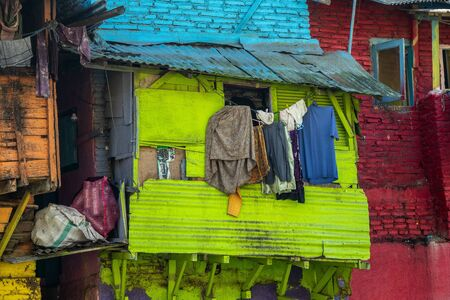 The wet laundry hangs on the washing line in the open air and in the sun. Behind the laundry, colorful facades of the houses are visible