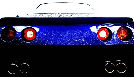 Rear view of a modern sports car. The red rear lights are visible and also the exhaust pipes under the car. Due to the high contrast in the photo, the display is futuristic