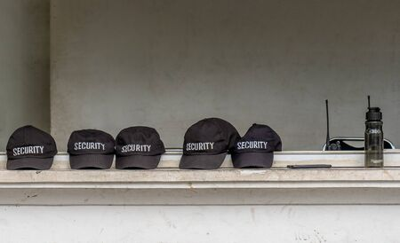 Several caps of security agents are next to each other in a row. The word security is clearly legible on the black caps Foto de archivo - 130817839