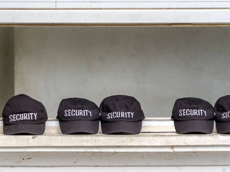 Several caps of security agents are next to each other in a row. The word security is clearly legible on the black caps Stock Photo - 130817845