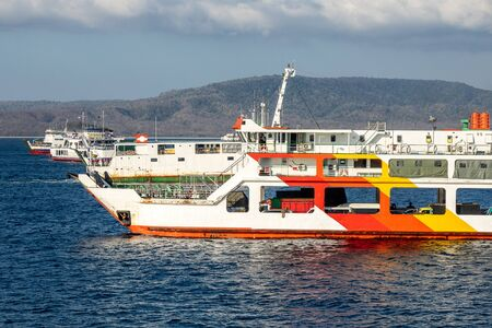 In the port of Banyuwangi in Java, Indonesia, there are many ferries to transport tourists to Bali. The boats look very rusty and decayed. There are many boats visible on the water.