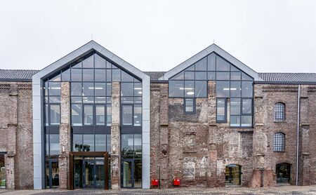 Dark brick facade of an old abandoned factory. The stones are damaged and outdated, but new windows have been installed so that the restored building can be used again. Reklamní fotografie