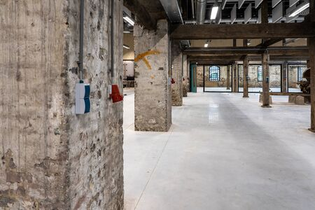 Interior of a former factory that has been restored. The old constructions and brick walls are visible, supplemented with restored and new parts. It continues to give a grungy and rundown impression.