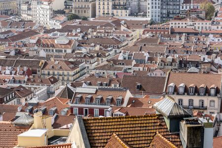 Panoramic image of the Lisbon skyline with the houses with red roof tiles and the sea in the background. The city is built on seven hills and therefore has many height differences.