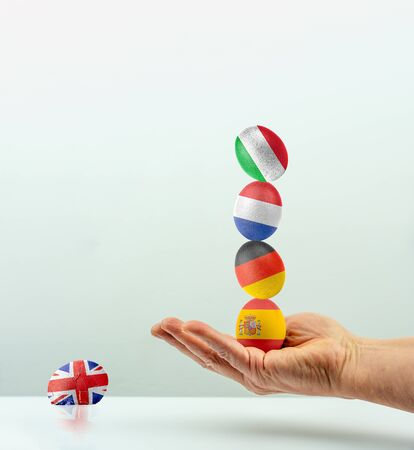 The unstable balance within the EU symbolized with eggs with the national flags. The English egg has fallen and broke as a symbol for Brexit Stock Photo