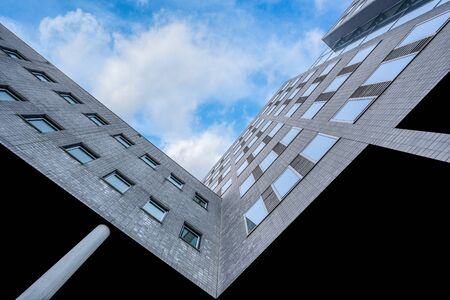 Low angle view of a facade of a corporate building under a blue sky