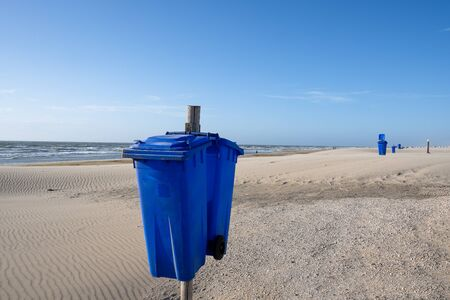 Blue trash cans on an empty and deserted sandy beach. In the background the sea is visible Standard-Bild