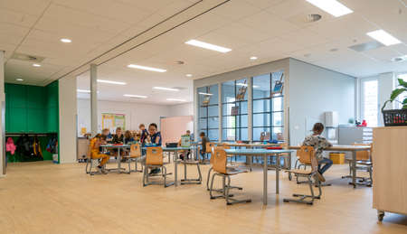 ARNHEM / NETHERLANDS - AUGUST 28 2020: Children in primary school work together in groups. They are located in a modern school building