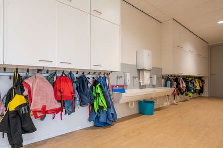 ARNHEM / NETHERLANDS - AUGUST 28 2020: Cloakroom with coats and backpacks in a school building for toddlers and young children
