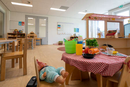 ARNHEM / NETHERLANDS - AUGUST 28 2020: Children in kindergarten play with toys. Other toys stored in cupboards, boxes and crates.