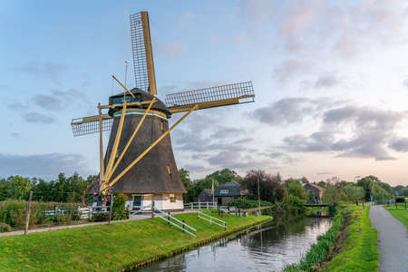 Traditional dutch windmill in a rural landscape next to a farm house and a stream of water