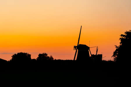 Silhouette of a traditional Dutch windmill against the red orange light of the rising or setting sun in a rural landscape Standard-Bild