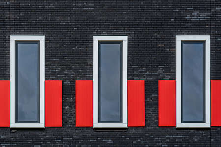 Fragment of a modern building facade with three windows in a row. Brick facade and red shutters