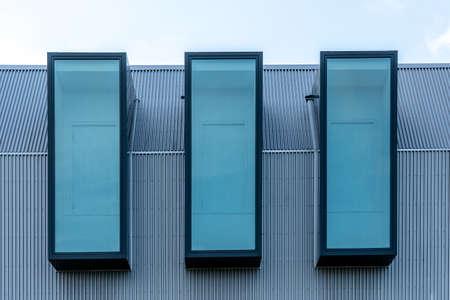 Fragment of a modern building facade with three windows in a row. Metal sheet facade Standard-Bild
