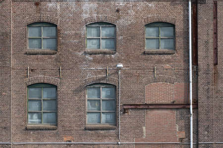 A fragment of an old and weathered facade of an old factory, made of masonry, steel and wooden frames. The old walls are cracked and the steel is corroded