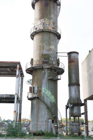 The remains of an old factory. The round steel chimney and the steel construction of the building are clearly visible