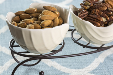 almond and pecan nuts in white, china bowls with metal stand Stok Fotoğraf