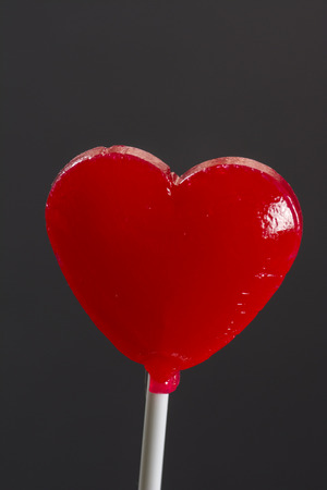 heart shaped,sweet,  red lollipop on the black  background