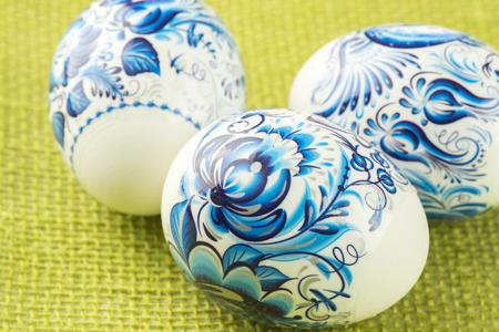 CLoseup, colorful Easter eggs on a green burlap. Reklamní fotografie