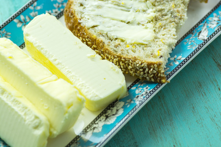 buttered: Fresh sticks of butter with buttered slice of bread