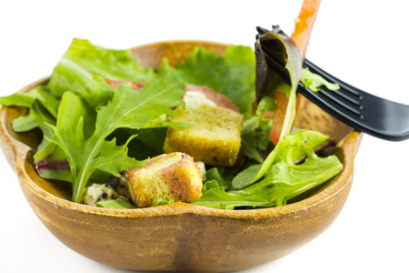 wooden handmade: Closeup natural, wooden, handmade  bowl with a fresh  green salad  on a white background.