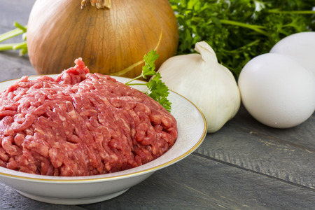 ground beef: Closeup eggs, onion, garlic and ground beef- ingredients for meatballs on a wood bacground. Stock Photo