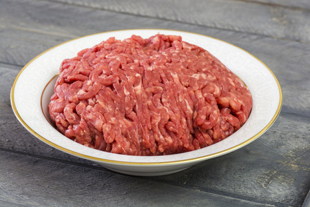 ground beef: Closeup plate with ground beef on the wood background.