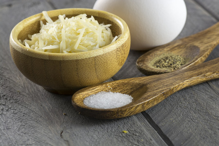 Egg and cup of grated parmesan and spoons with salt and black pepper.