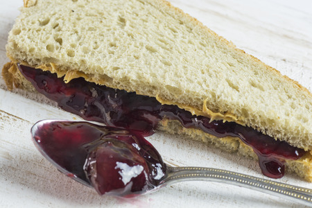 jelly sandwich: Closeup of peanut butter and jelly sandwich on a wood.