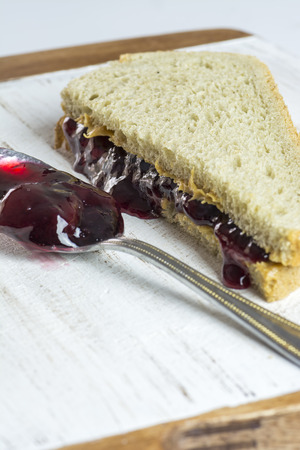 peanut butter and jelly sandwich: Closeup of peanut butter and jelly sandwich on a wood.