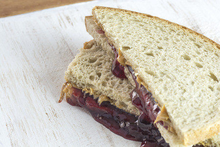 peanut butter and jelly: Closeup of peanut butter and jelly sandwiches on a wood.