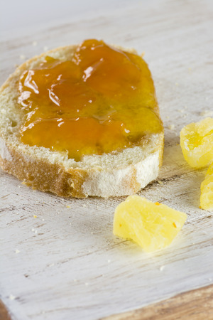 sugared: Closeup of  jelly sandwich and a pieces of sugared pineapple on a wood.
